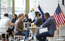 Students sitting at tables. talking