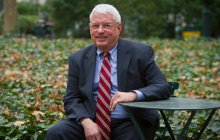 President Scott Evenbeck sitting on a chair in Bryant Park, facing the camera