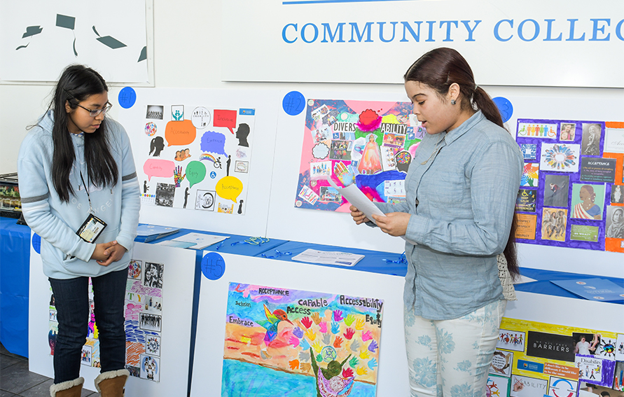 Students Paola Rojas and Kathleen Hernandez present original artwork in celebration of DiverseABILITY at the April 2 Disability Awareness Month kick-off event.