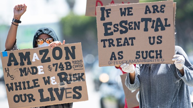 """Person holding a cardboard sign that reads, """"If we are essential, treat us as such."""""""