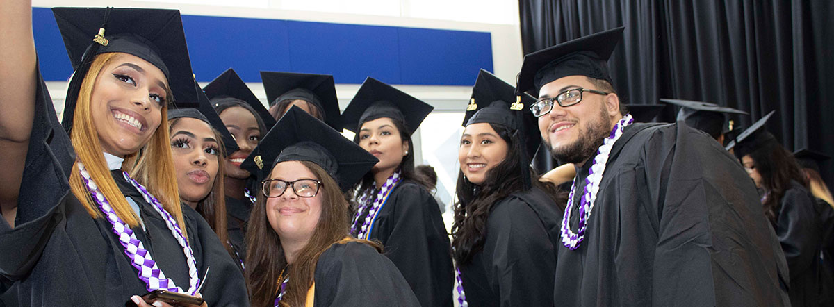 Group of students wearing caps and gowns posing for a selfie
