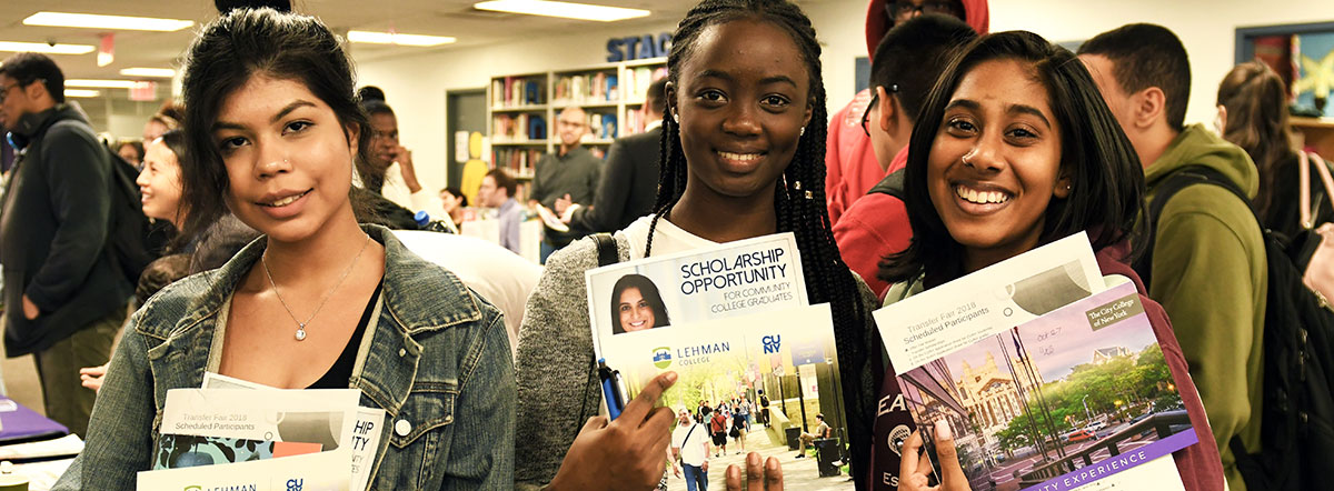 Three students showing college pamphlets