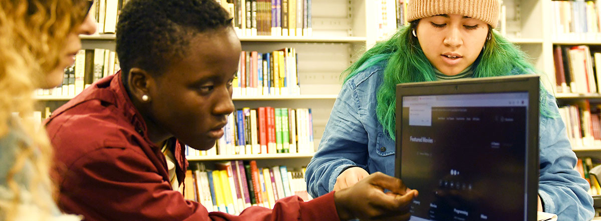 Students looking at a laptop in the library