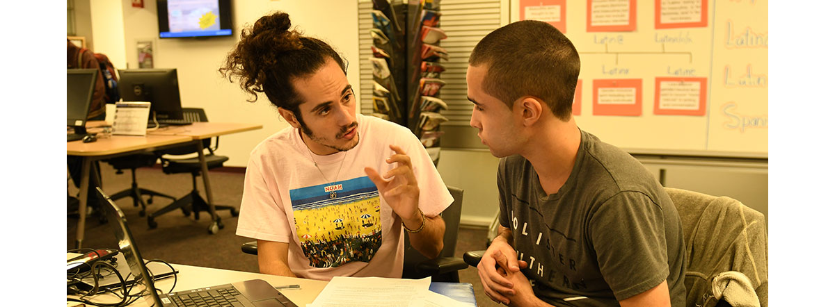 Two students talking at a table