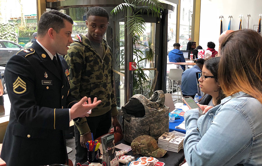 Student talking to army officers at a job fair