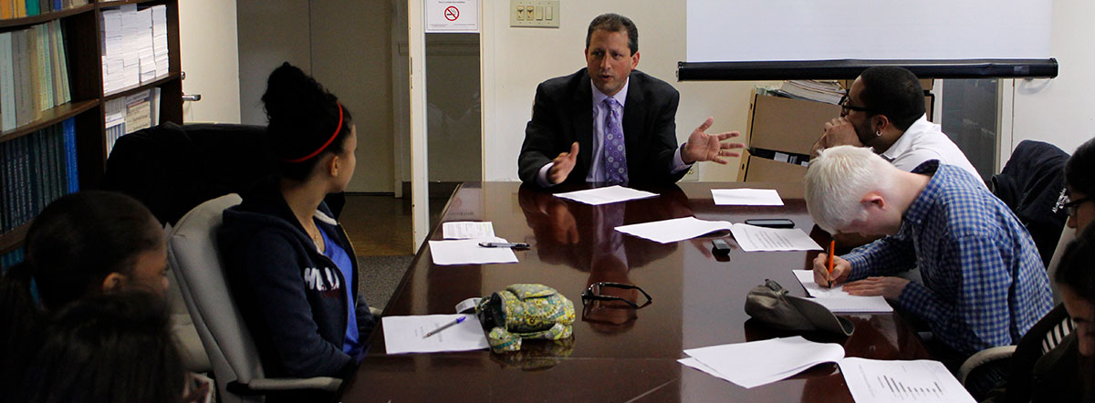 Students sitting at a conference table listening to a person sitting at the head of the table