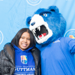 Stella the Grizzly with her arm around a student