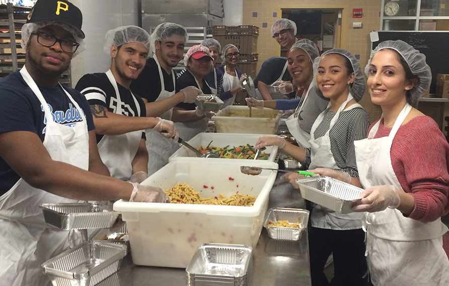 Group photo of students helping to prepare food in a kitchen