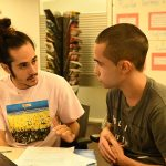 2 students talking at a desk