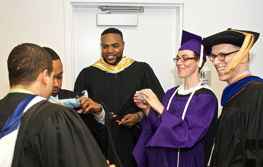 Group of faculty in graduation regalia in conversation