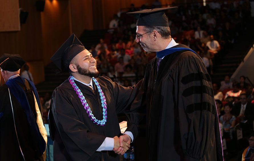 Graduate shaking the Provost's hand on stage