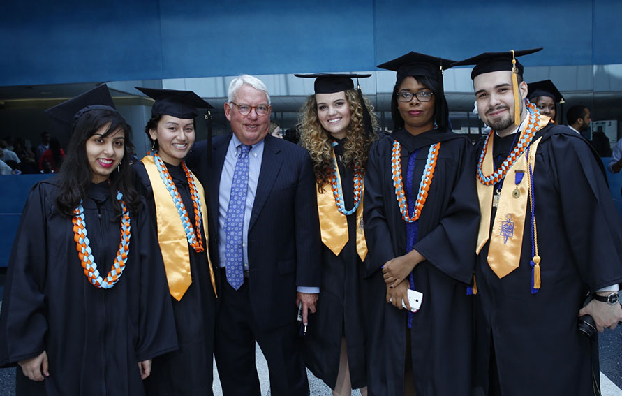President Evenbeck with a group of students at the Inaugural Commencement ceremony